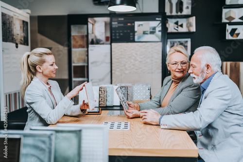 Fototapeta Senior couple are buying ceramic tiles and utensils for their home and female seller is helping them to make right decision. obraz