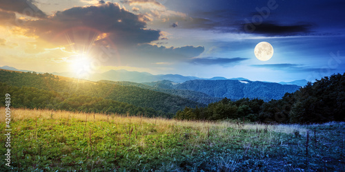 Obraz day and night time change concept above summer mountain landscape. beautiful scenery with sun and moon. beech forest and grassy alpine meadows on the hills. clouds on the gorgeous sky - fototapety do salonu