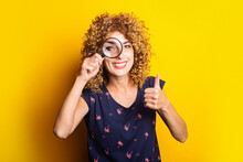 Curly Young Woman Looking At Camera Through Magnifying Glass Showing Thumbs Up Gesture On Yellow Background.