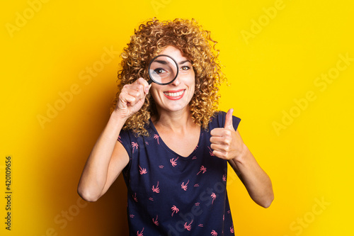Photographie curly young woman looking at camera through magnifying glass showing thumbs up gesture on yellow background