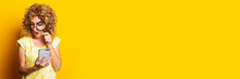 Shocked Curly Young Woman Looking With A Magnifying Glass Into The Phone On A Yellow Background. Banner