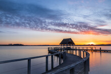 Swinging Pier Construction And Shelter With Thatched Roof At Beautiful Colorful Dawn Just Before Sunrise Under Cloudy Sky At Lake Hemmelsdorf, Schleswig-Holstein, Northern Germany