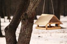 Handmade Small Wooden Bird House Feeder In The Park On The Tree For Feeding Wild Birds, Winter Season, Snow On The Ground