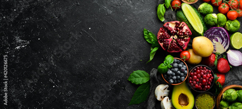 Fototapeta Healthy eating concept: vegetables and fruits on black stone background. Top view. Free space for your text. obraz