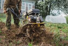 A Man Intensively Plows His Vegetable Garden Motor Cultivator