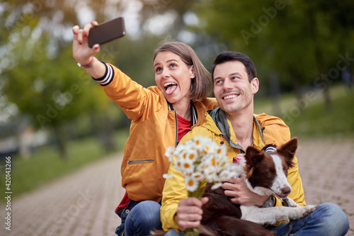 Fototapeta close up of young couple taking selfie with their dog in a lap, making funny faces obraz
