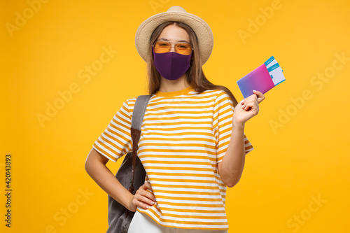 Fototapeta Immunity passport. Happy young woman tourist is ready to travel, holding tickets to safe flight after end of coronavirus lockdown or having negative covid test obraz