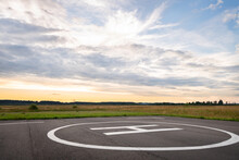 View Of The Private Helipad On A Warm Summer Evening. An Asphalt Helipad Against The Backdrop Of A Green Field And A Cloudy Evening Sky.