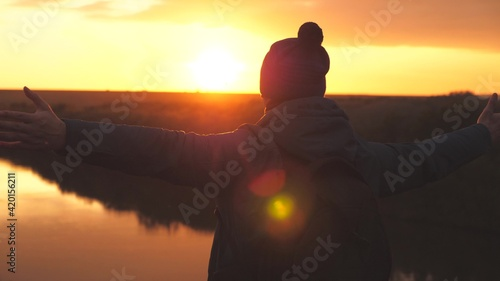 Foto Man traveler whirls at sunset and laughs, adventurer in free flight of fantasy,