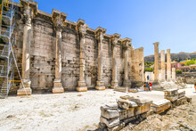 Tourists Sightsee At The Ancient West Wall Of Hadrian's Library At The Roman Agora Near The Plaka District In Athens, Greece.