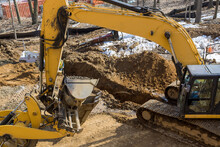 Excavator Dig Trench At Construction Site Laying Sewer Wells And Sewer Pipes