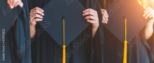Fotografiet Close up group of graduates holding a hat At the graduation ceremony at the univ