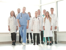 Group Of Confident Doctors Striding In The Hospital Corridor
