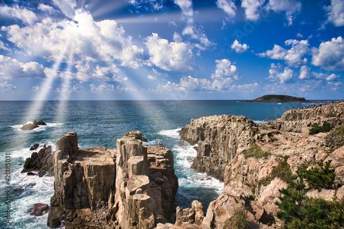東尋坊の断崖に差し込む太陽光線 Fotobehang