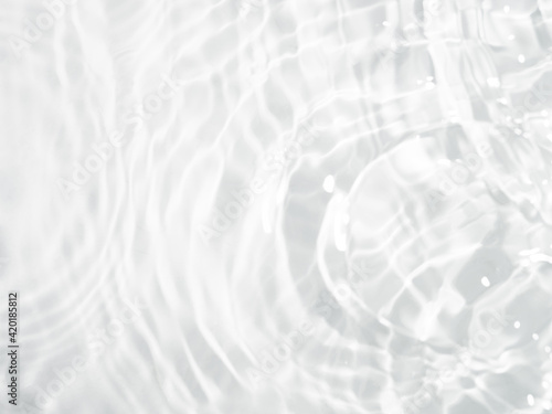 Obraz Blurred ripple water texture on white background. Shadow of water on sunlight. Mockup for product, spa or travel background. Marble water surface as wallpaper background - fototapety do salonu