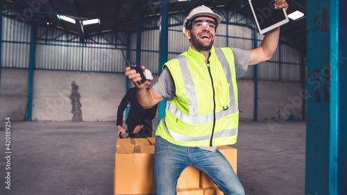 Funny factory workers dance in the factory . Happy people at work .