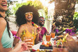 canvas print picture - Multiracial group of friends having fun at backyard home party - Young people laughing together drinking cocktails at bar restaurant - Focus on black woman