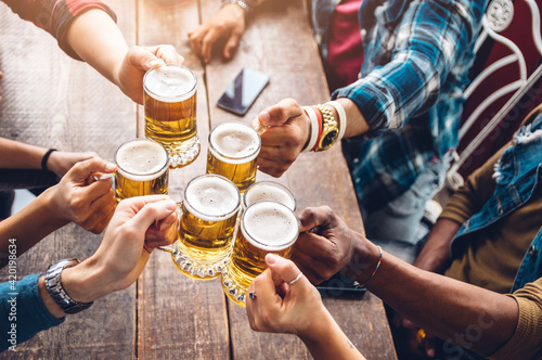 Photo Group of people enjoying and toasting a beer in brewery pub - Friendship concept