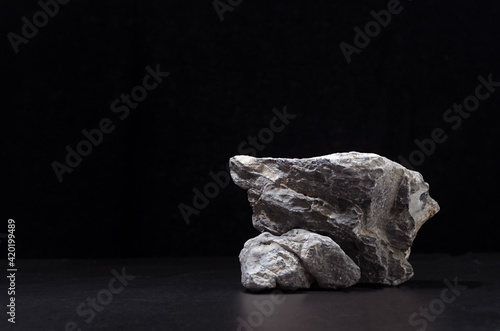 Luxury natural stone podium for showing packaging and product on black background, copy space.