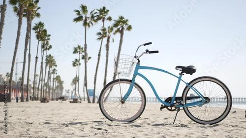 Fotografia Blue bicycle, cruiser bike by sandy ocean beach, pacific coast near Oceanside pier, California USA