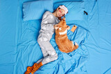 Happy girl and her favorite domestic pet play together in bed have good relationships enjoy morning time lasy day. Positive redhead woman wears pajama sleepmask spends free time with favorite dog