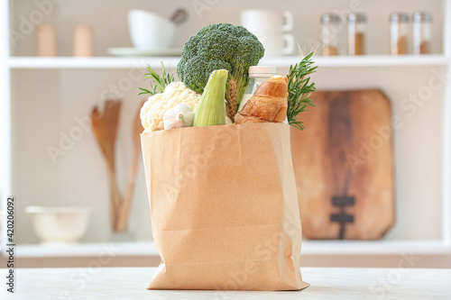 Paper bag with different products on table in kitchen