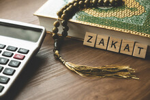 Concept Of Zakat In Islam Religion. Selective Focus Of Wooden Alphabet, Calculator, Rosary Beads And Quran On Wooden Background.