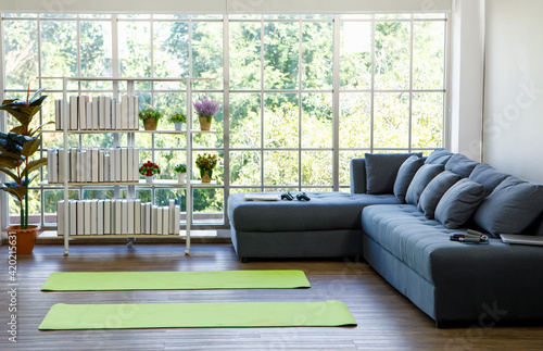 Foto Two yoga mat on flloor nearby sofa in living room with green tree in background