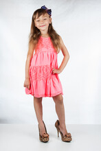 Cute Little Girl In High-heeled Shoes Posing On A White Background.