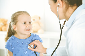 Doctor examining a child by stethoscope. Happy smiling girl patient dressed in blue dress is at usual medical inspection. Medicine concept