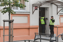 Two Policemen Are Standing In Front Of The Building's Entrance Door