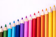 a row of colored pencils on a white background