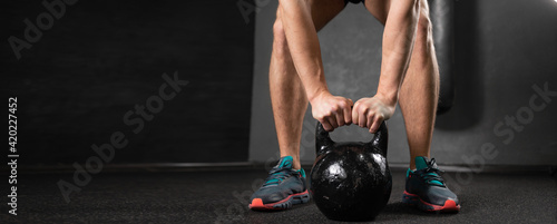 Obraz Male athlete in the gym lifts a heavy kettlebell with both hands. Legs and arms of a sports man on the right and place for text. - fototapety do salonu