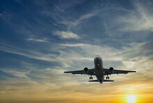 The Plane Against The Blue Sunset Sky. The Setting Sun