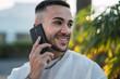Chico joven atractivo en zona con palmeras y usando el smartphone