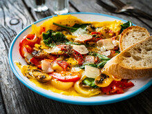 Delicious Breakfast - Scrambled Eggs With Onion, Bell Pepper, Parmesan And Mix Of Young Vegetable Leaves On Wooden Table