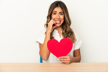 Young Caucasian Woman Holding A Valentines Day Heart Isolated Biting Fingernails, Nervous And Very Anxious.