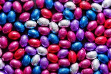 A Portrait Of A Lot Of Colorful Chocolate Easter Eggs Wrapped In Colored Tin Foil. There Are Red, Blue, White, Purple And Pink Eggs All With Their Own Flavor And Taste.