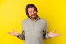 Middle Age Caucasian Man Isolated On Yellow Background Doubting And Shrugging Shoulders In Questioning Gesture.