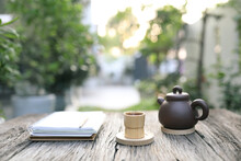 Brown Bamboo Cup And Teapot And Notebook On Grunge Wooden Table At Outdoor