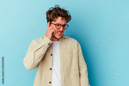 Obraz Young caucasian man wearing eyeglasses isolated on blue background covering ears with hands. - fototapety do salonu