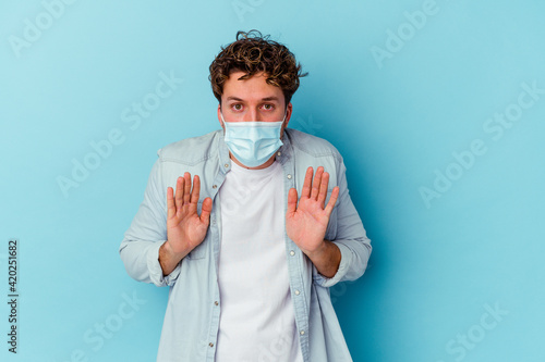Obraz Young caucasian man wearing an antiviral mask isolated on blue background rejecting someone showing a gesture of disgust. - fototapety do salonu