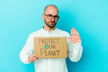 Young Caucasian Bald Man Holding A Protect Our Planet Placard Isolated On Purple Background Standing With Outstretched Hand Showing Stop Sign, Preventing You.