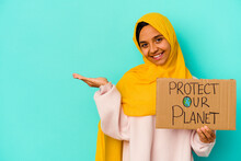 Young Muslim Woman Holding A Protect Our Planet Isolated On Blue Background Showing A Copy Space On A Palm And Holding Another Hand On Waist.