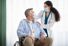 Young Doctor And Disabled Senior Man In Wheelchair Wearing Face Masks During Covid-19 Pandemic At Retirement Home