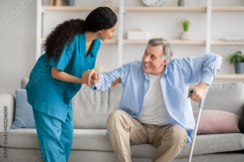Photo Young nurse helping elderly man with crutches to get up from sofa indoors