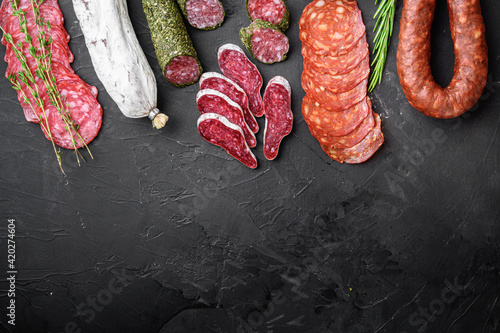 Fototapeta Set of dry cured salami, spanish sausages, slices and cuts on black background,