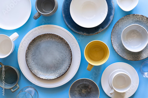 Leinwand Poster Blue background with empty tableware, plates and cups of different color