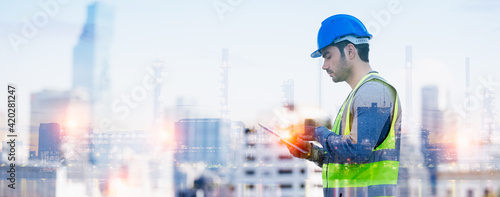 Fotografiet Panoramic double exposure of smart engineer maintenance in solar power plant checking installing photovoltaic solar modules with digital tablet with Oil and gas refinery industry plant background