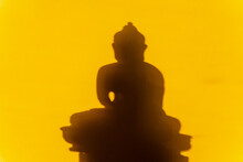 Buddha On A Yellow Background. Figurine Of A Buddha Statue Brown. Jade Buddha, Meditation, Yoga